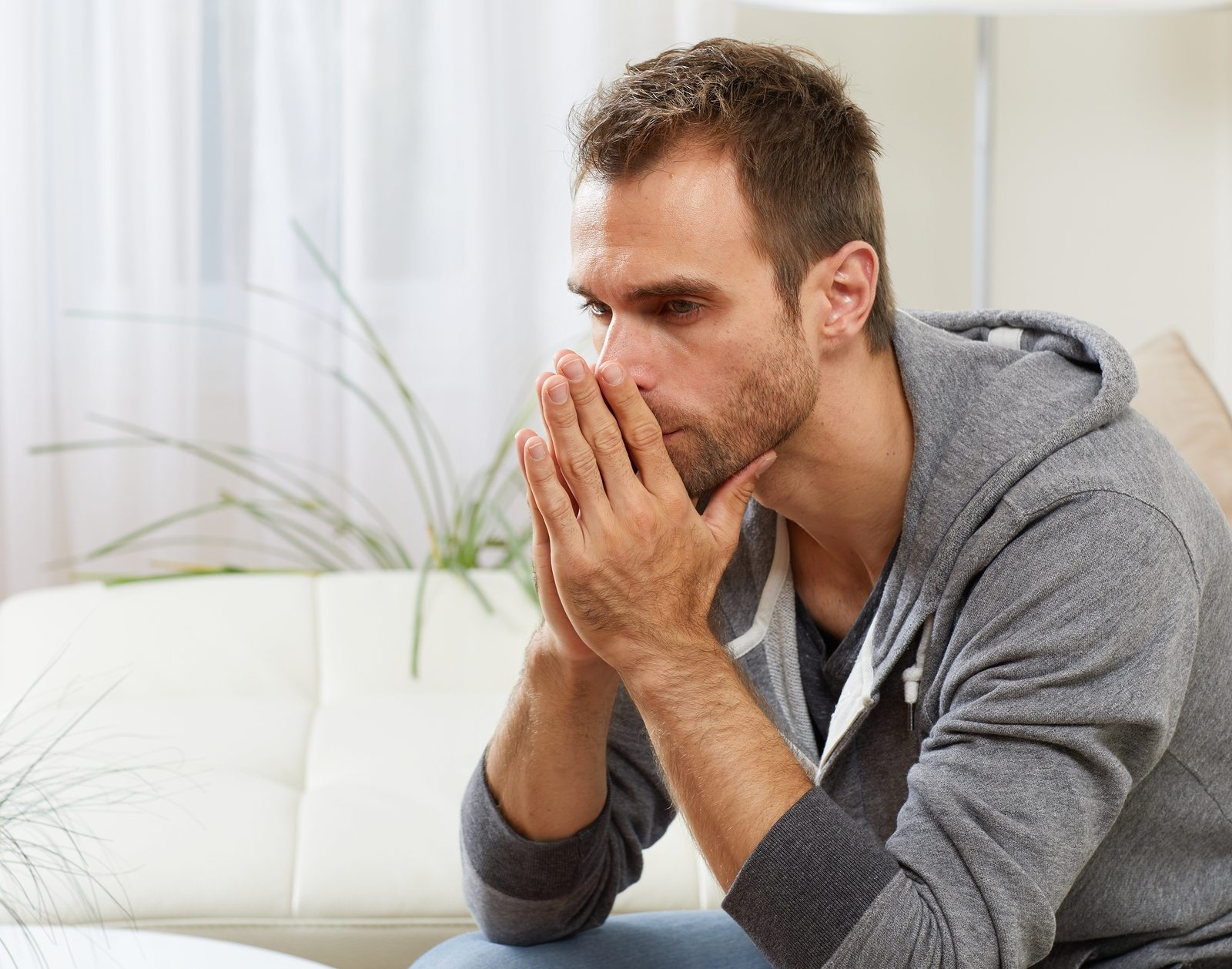 Anxious man with hands in front of face