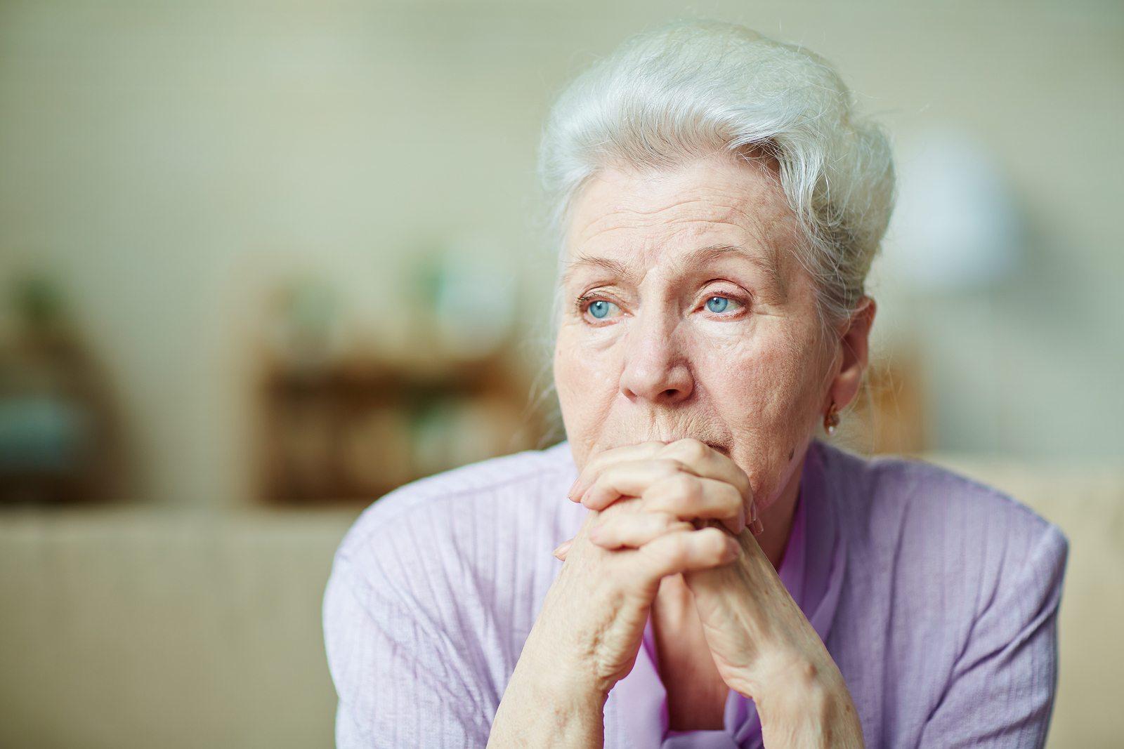 Sad senior woman sitting at home