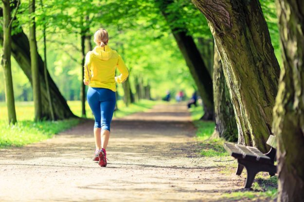 Woman running and walking in beautiful city park. Young girl jogging in bright forest outdoors summer nature. Endurance concept with working out and exercising in inspirational green woods landscape.