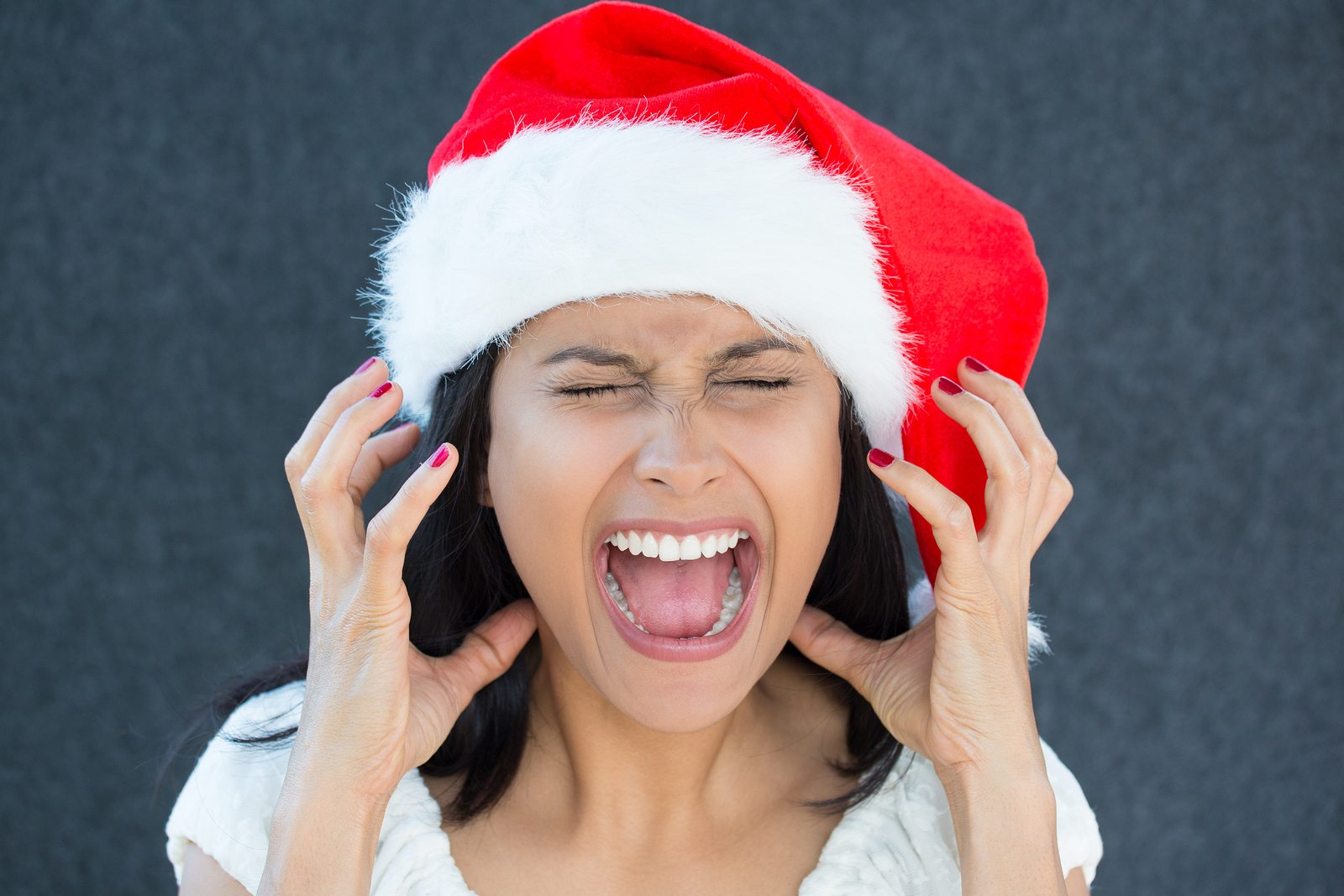 Closeup portrait of a cute Christmas woman with a red Santa Claus hat white dress screaming out loud frustrated eyes shut in rage. Negative human emotion on an isolated grey background.