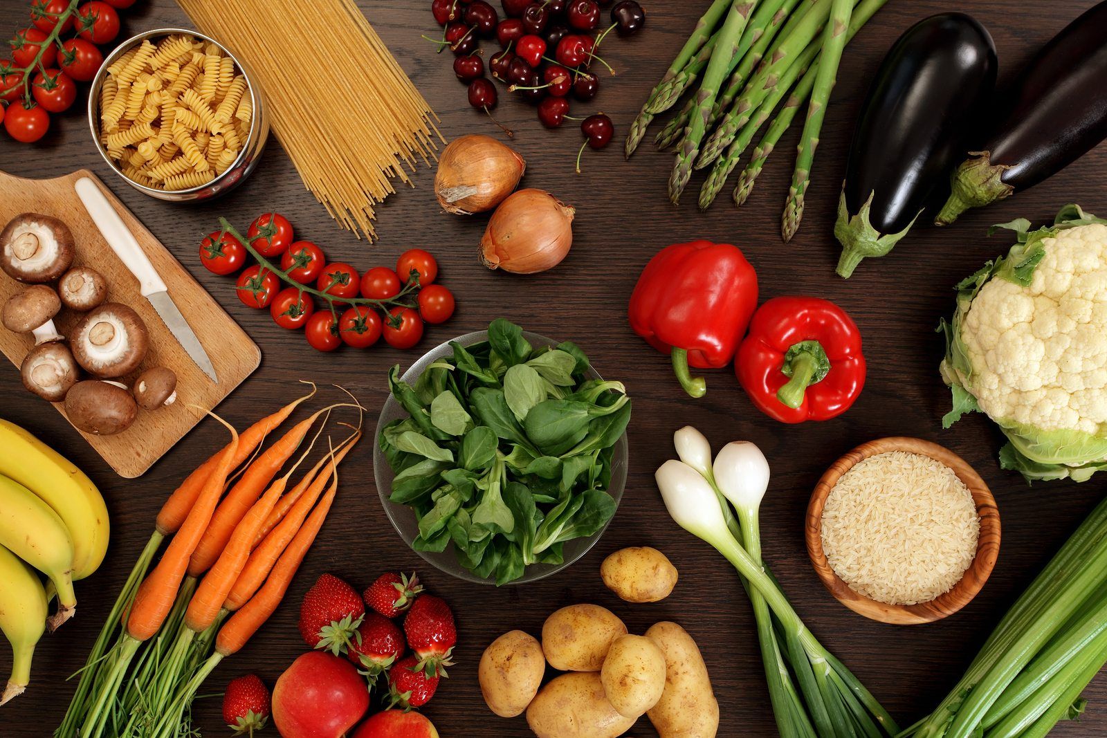 Photo of a table top full of fresh vegetables fruit and other healthy foods.