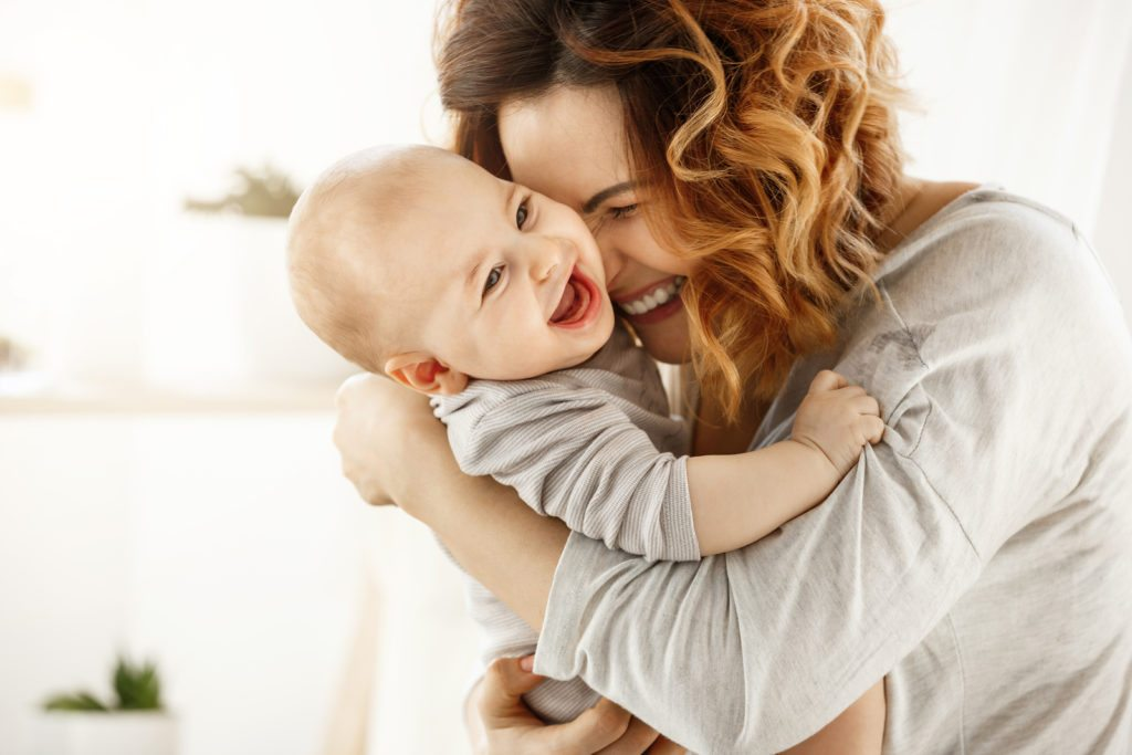 Portrait of happy laughing baby hugging with cheerful young smiling mother. Scene of pure love and happiness. Family, motherhood and lifestyle concept