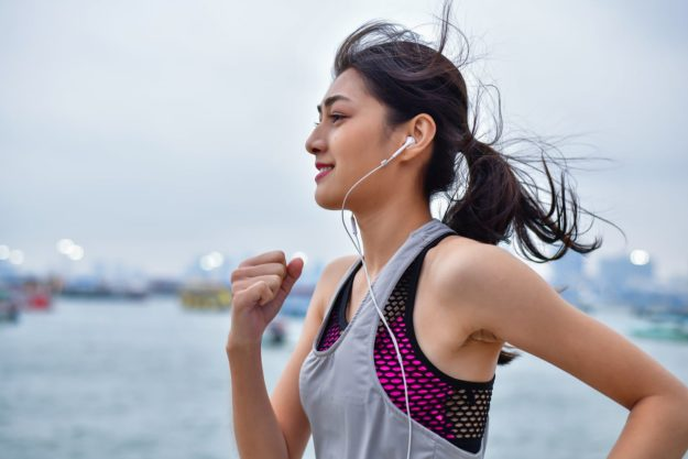 Young woman running with headphones in