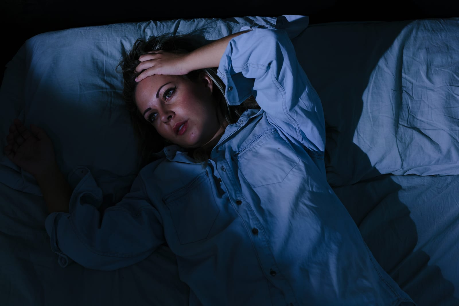 Sleep disorder insomnia. Young blonde woman lying on the bed awake