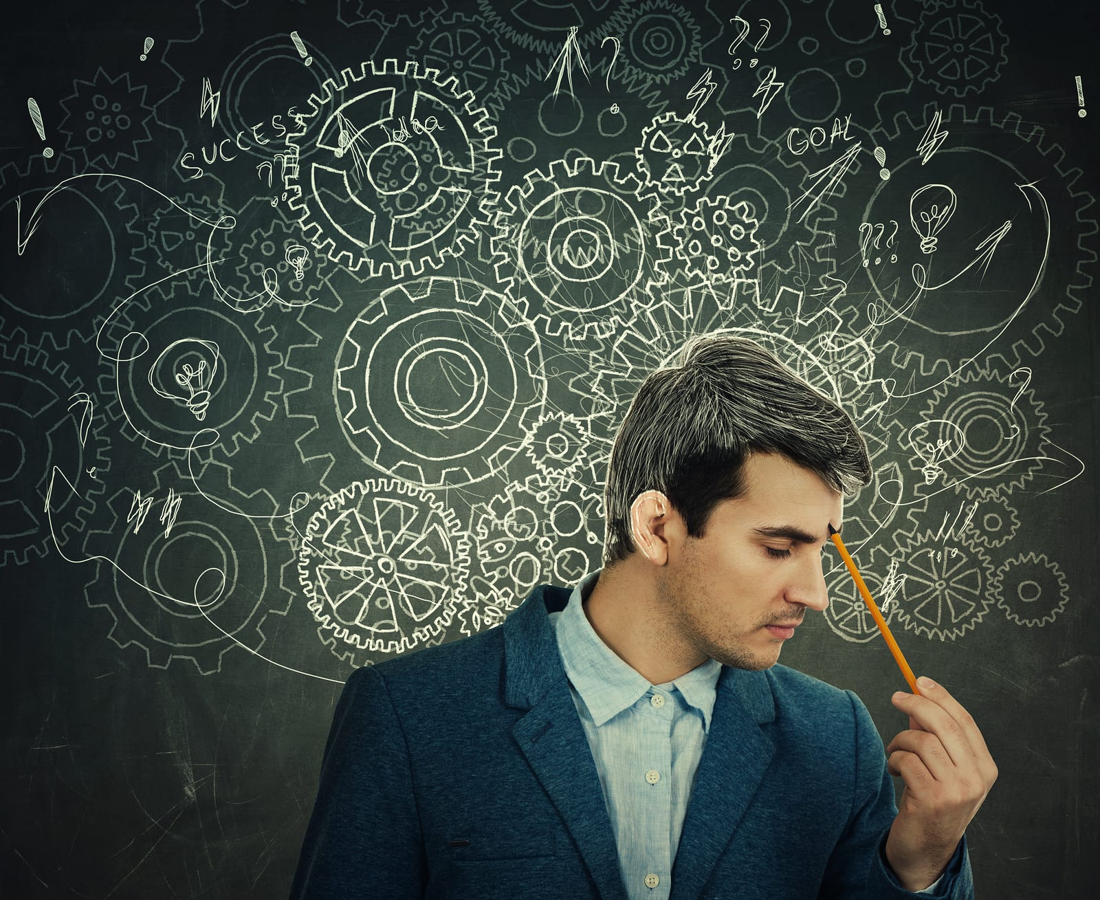 Hard thinking serious man over blackboard background gear brain arrows and mess as thoughts. Concept for mental, psychological development.