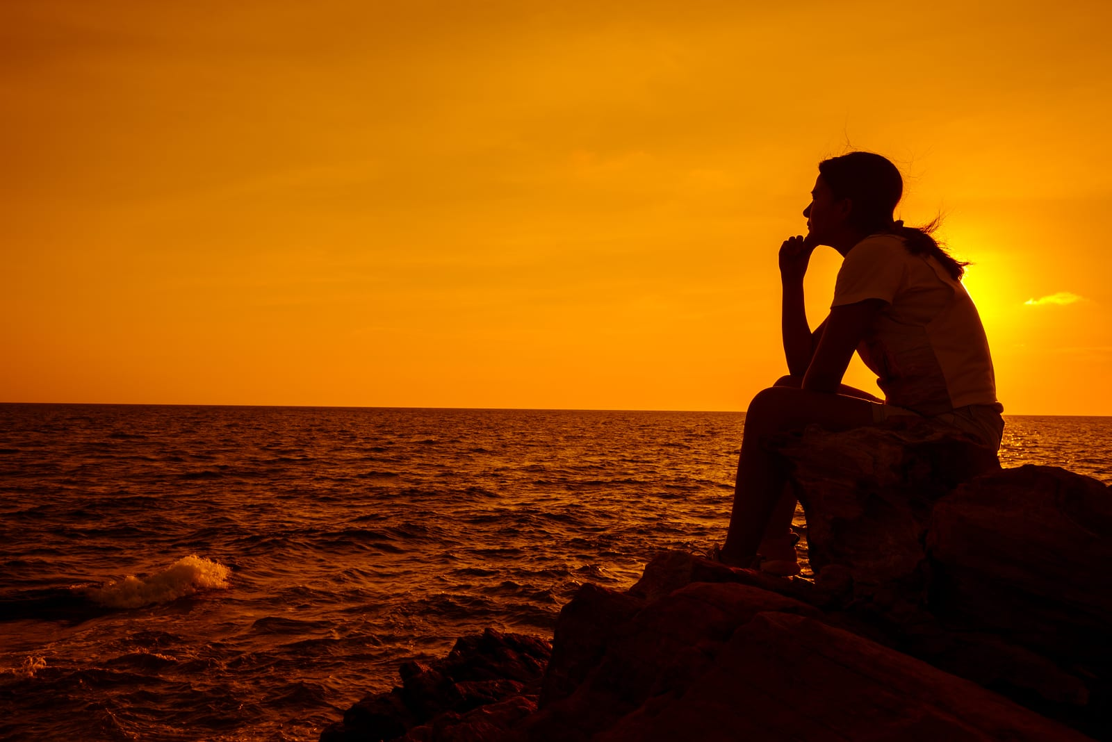 Silhouette women sitting alone on the rock. Mental health, PTSD and suicide prevention.